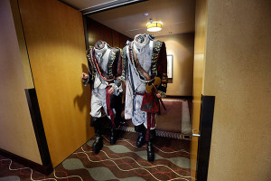 Two men dressed as headless characters get out of a hotel lift